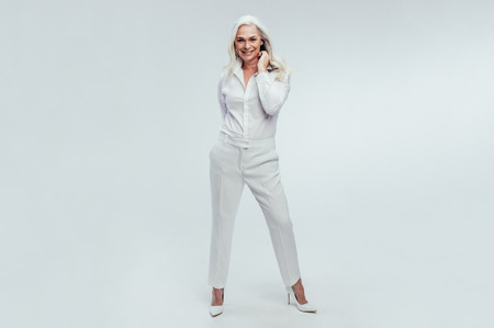 Photo pour Full length portrait of beautiful senior woman standing over white background. Stylish mature woman posing in white casuals. - image libre de droit