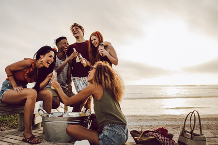 Foto de Smiling young woman with beer bottle and friends standing by on the beach. - Imagen libre de derechos