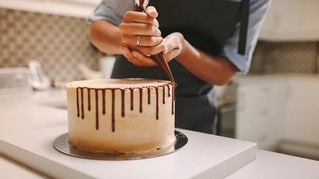 Photo pour Close up of hands of a female chef with confectionery bag squeezing liquid chocolate on cake. - image libre de droit
