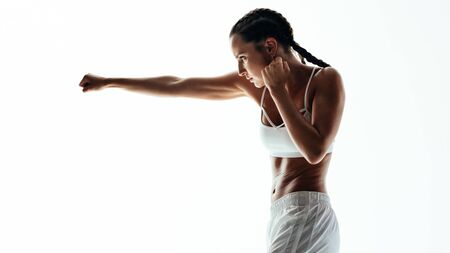 Photo pour Fitness woman doing boxing workout. Female practicing boxing, throwing a punch in front against white background. - image libre de droit