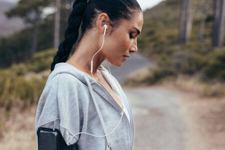 Foto per Side view of a female athlete wearing earphones. Woman listening to music during workout outdoors in morning. - Immagine Royalty Free
