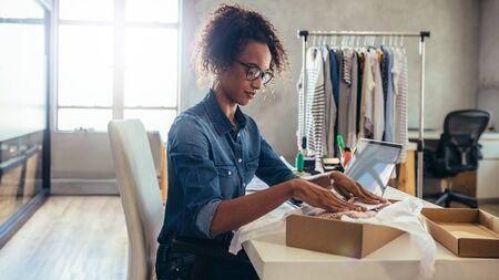 Foto de Woman online entrepreneur packing parcel box at office. Woman seller preparing product for delivery. - Imagen libre de derechos