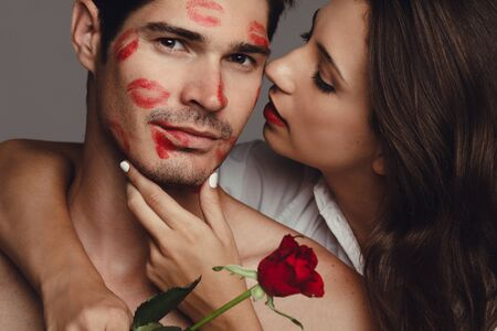 Photo pour Close up of woman kissing her boyfriend. Man kissed by girlfriend with lipstick kiss marks on the face. - image libre de droit