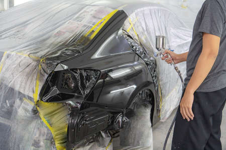 Photo pour Man with protective clothes and mask painting car using spray compressor - image libre de droit