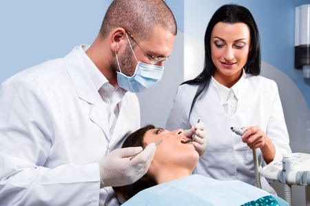 Male dentist with assistant and patient at dental clinic