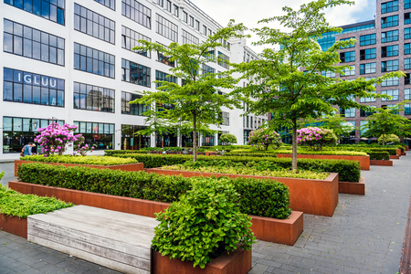 Photo pour Eindhoven, Netherlands- May 24, 2015: Eindhoven downtown. Lush bushes and benches in the office complex park - image libre de droit