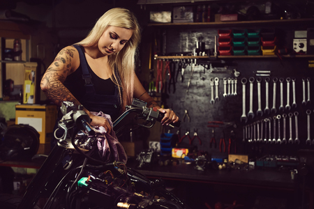 Foto de Blond woman mechanic working in a motorcycle workshop - Imagen libre de derechos