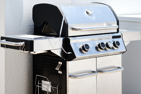 Foto de Stainless steel gas grill bbq barbecue. Cooking meat, fish, vegetables in summertime gatherings - Imagen libre de derechos