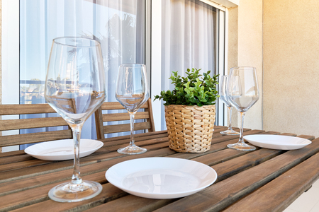 Photo pour Close up white empty plates wine glasses, wooden table setting at home in outdoors terrace, plant on weave pot no people - image libre de droit