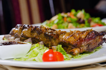 Close Up of Rack of Grilled Pork Ribs Served on Plate in Restaurant