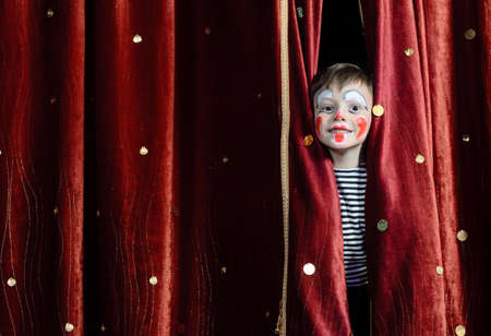 Photo for Young Boy Wearing Clown Make Up Peering Out Through Opening in Red Stage Curtains - Royalty Free Image