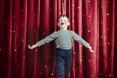 Photo for Young Boy Dressed as Clown Performing on Stage with Open Arms and Open Mouth as if Singing or Acting - Royalty Free Image