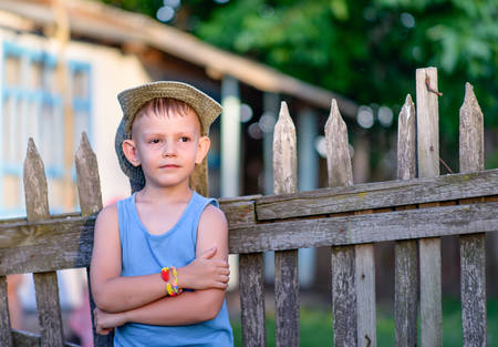 Photo for Cute Young Boy Leaning Against the Wooden Fence with Arms Crossed Over his Stomach, Showing a Pensive Facial Expression. - Royalty Free Image
