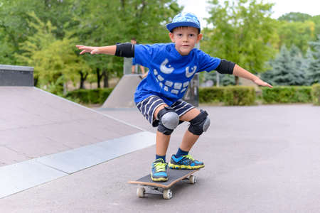 Photo pour Young boy showing off on his skateboard striking a stylish pose as he practices his skill at the skate park - image libre de droit