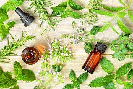Foto de fresh herbs, leaves, flowers and massage oils on the wooden board - Imagen libre de derechos