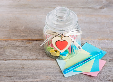 Photo for Glass jar with handmade wooden hearts decorations and ribbon near a stack of colored papers and a blue pen. - Royalty Free Image