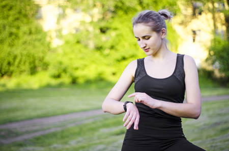 Foto per A young girl uses a fitness tracker. Smartwatch. Measurement of pulse, distance, time. The notice came. Blonde woman in black sports clothes. Playing sports in the Park. Photo. - Immagine Royalty Free