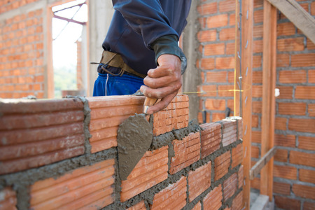 Foto de Worker building masonry house wall with bricks - Imagen libre de derechos
