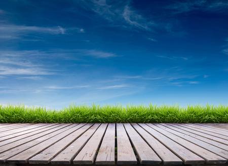 Photo pour wooden terrace with fresh spring green grass and blue sky - image libre de droit