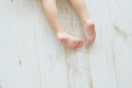 Foto de The childs legs on a floor. Top view. Nurseries of a foot. - Imagen libre de derechos