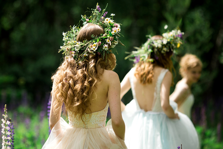 Photo for Wedding. The bride in a white dress standing and embracing bridesmaids - Royalty Free Image