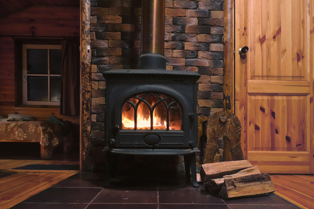 Foto de Fragment of the interior of a country house. The iron furnace is heated. There is wood near the stove. It's dark outside the window. - Imagen libre de derechos