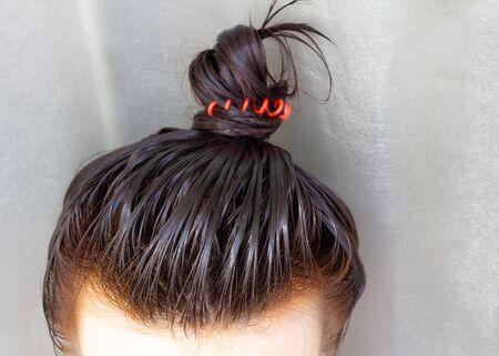 Foto de The girl puts the balm on her head. She gathered her hair into a bun. - Imagen libre de derechos