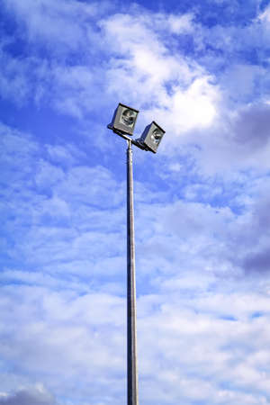 Photo for Sport field lighting outdoor floodlight straight on angle against blue sky - Royalty Free Image