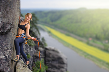 Female extreme climber conquers steep rock over the river