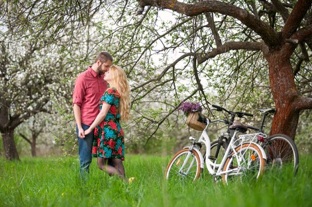 Romantic couple stand near the bicycles and tree holding hands in spring garden. Woman with long blond hair wearing flowered dress and man in a red shirt and jeans