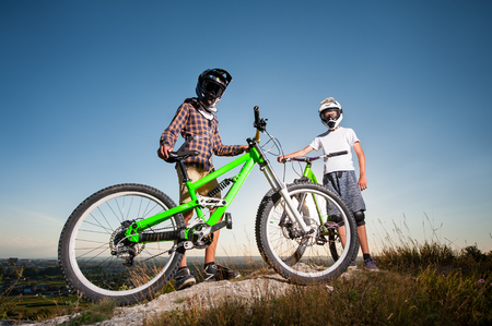 Two guys wearing in helmets and glasses standing with the mountain bikes on the hill under blue sky and looking into the camera. Bottom view