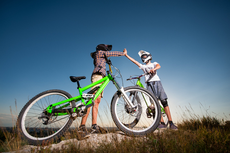 Two male bikers give high five for each other standing with the mountain bicycles on the slope under blue sky. Cyclists are wearing sportswear helmet and glasses. Bottom view