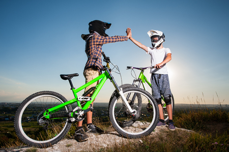 Two men give high five for each other standing with the mountain bicycles on the hill under blue sky. Cyclists are wearing sportswear helmet and glasses. Wide angle view