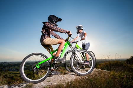 Two young cyclists wearing in helmets and glasses stay on the mountain bikes on the top of the mountain under blue sky and getting ready to ride downhill. Bottom view