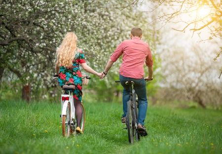 Family riding bicycles in the spring garden and holding hands. Girl with long blond hair wearing flowered dress and man in a red shirt. Rear view