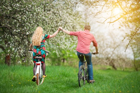 Active couple ride bicycles in the spring garden back to camera and holding hands. Woman with long blond hair wearing flowered dress and man in a red shirt
