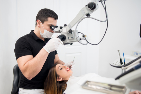 Foto de Male dentist with dental tools - microscope, mirror and probe checking up patient teeth at dental clinic office. Medicine, dentistry and health care concept. Dental equipment - Imagen libre de derechos