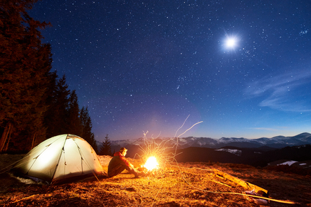 Photo pour Male tourist have a rest in his camp at night, sitting near campfire and tent under beautiful night sky full of stars and the moon and enjoying night scene in the mountains - image libre de droit