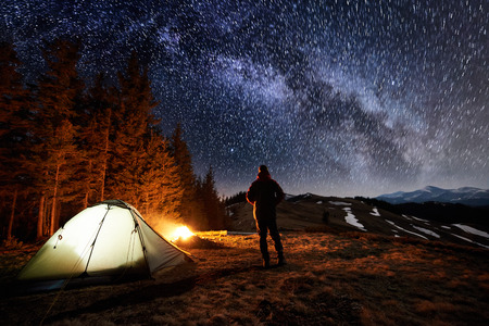 Photo pour Male tourist have a rest in his camp near the forest at night. Man standing near campfire and tent under beautiful night sky full of stars and milky way, and enjoying night scene. Long exposure - image libre de droit
