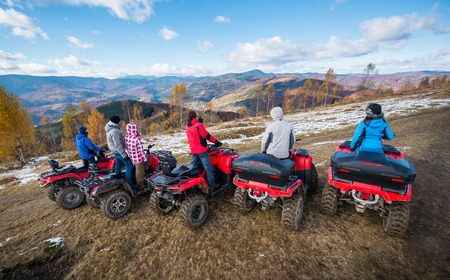 Photo pour Rear view of a group of people on red quad bikes at hill enjoying open views of the mountains under the blue sky in autumn - image libre de droit