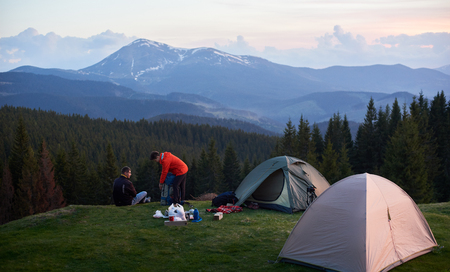 Photo pour Male and female tourists in the camping near two tents while hiking together with their backpacks. On the background beautiful forests and mountains. Carpathians mountains, Ukraine - image libre de droit