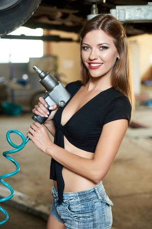 Photo pour Smiling female mechanic is posing with an automatic screwdriver in her hands - image libre de droit