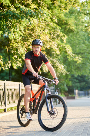 Handsome male biker in cycling sportswear and protective helmet riding on bike near green park. Concept of healthy lifestyle, sport advertising, outdoor activities