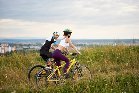 Two cyclists ride on a hill in the grass with wild flowers in the distance the city and mountains are moving. The man looks at the woman with a smile. Both are dressed in sports clothes and helmets