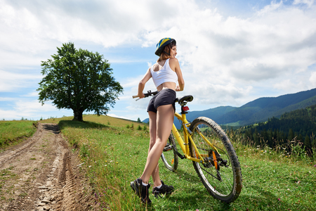 Foto de Wide angle view of attractive female cyclist riding on yellow bicycle on a rural trail in the mountains, wearing helmet. Big tree and cloudy sky on the background. Outdoor sport activity - Imagen libre de derechos
