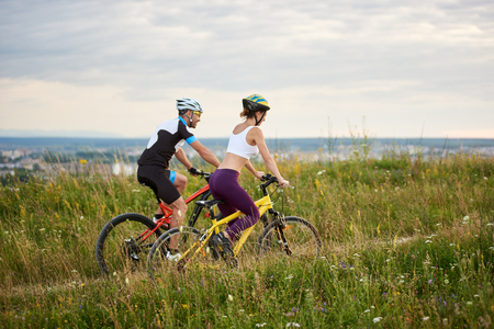 Two happy cyclists - man and woman riding on a hill in the grass with wild flowers, city and mountains in the distance. Both are dressed in sports clothes and helmets