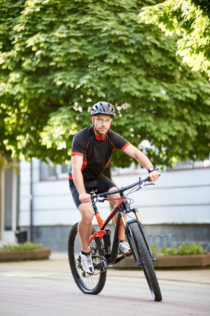 Young male bicyclist in cycling sportswear and protective helmet, looking at camera, riding bike down empty city center alley surrounded by green trees. Sportsman training outdoors improving skills.