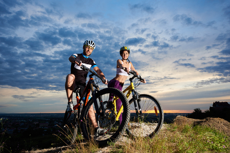 Young people on mountain bikes on top of a hill under a magic sky at sunset. The guys are dressed in sports clothes and helmets and look at the camera