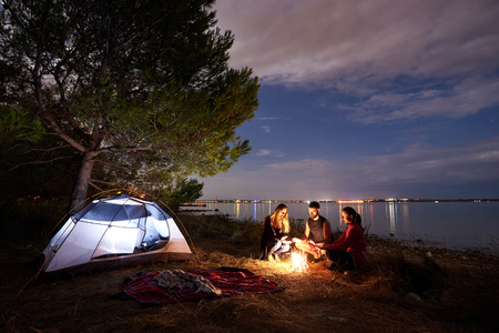 Foto de Group of three tourists, young man and women sitting on lake shore at bonfire near tourist tent under tree. Quiet water surface and evening sky on background. Tourism, friendship and camping concept. - Imagen libre de derechos