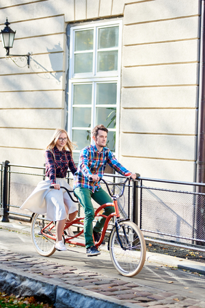 Foto de Young active smiling traveler couple, handsome bearded man and pretty blond woman in glasses riding together tandem bicycle along paved sidewalk on bright sunny autumn day by ancient buildings. - Imagen libre de derechos